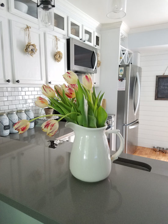 gray quartz counters with white cabinets and subway tile backsplash