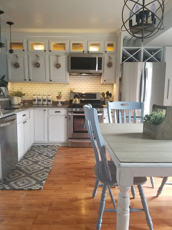 white kitchen cabinets, gray counters and subway tile backsplash
