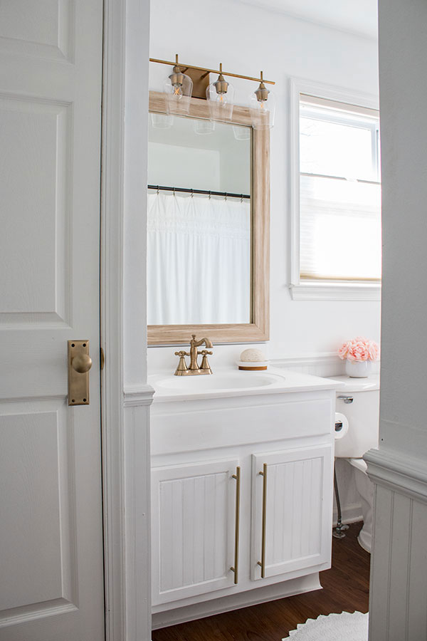 This-builder-grade-bathroom-got-a-makeover,-white-vanity-framed-mirror-and-gold-accents