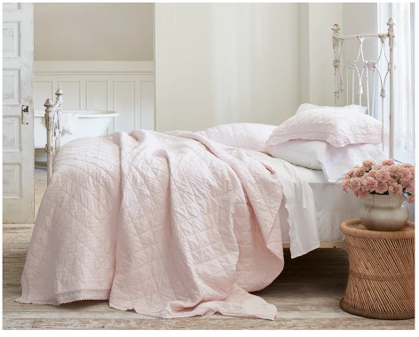 light pink quilt with crocheted trim