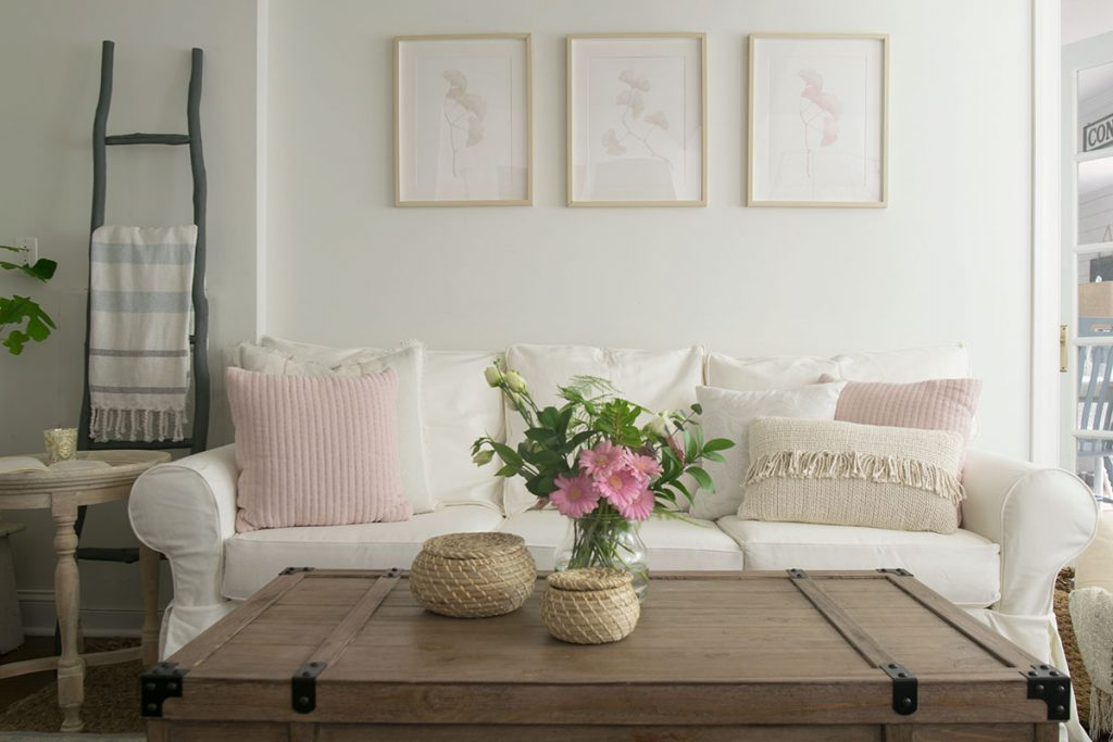 neutral living room decorating, white slipcover sofa and neutral wall decor