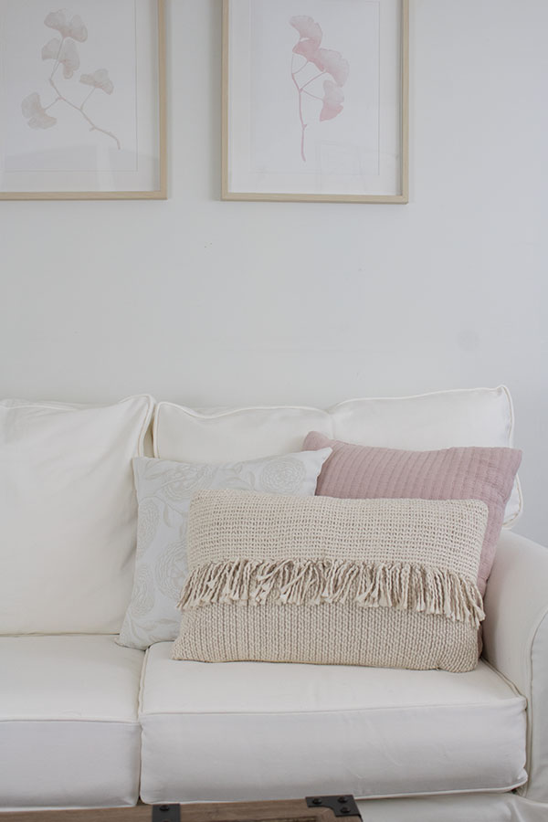 white sofa with slipcover and neutral wall art