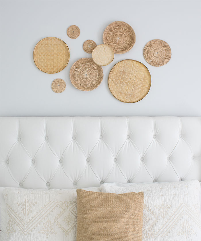 gallery wall of baskets above bed