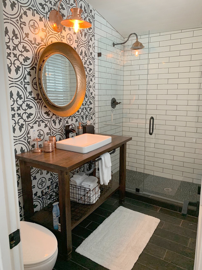Rustic bathroom vanity with copper accents and patterned tile