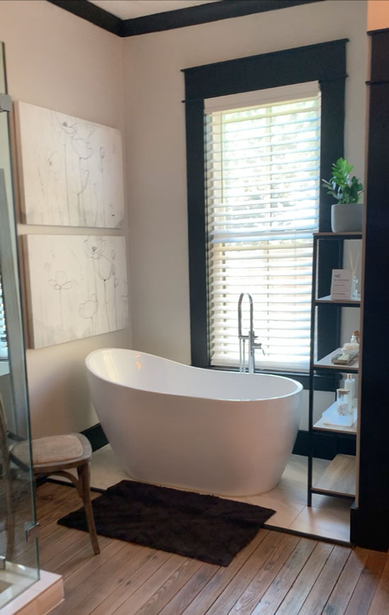 bathroom with black molding and freestanding tub