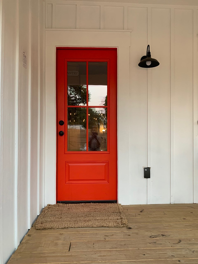 red farmhouse door board and batten porch