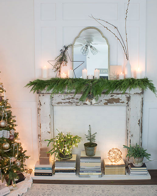 Christmas mantel with fresh cedar garland, candles and stacked books