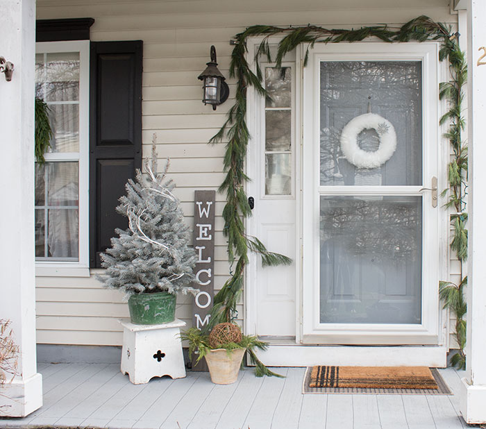 Pine garland hung around front door exterior.